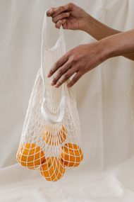 person-holding-four-oranges-in-white-net-bag-3737618